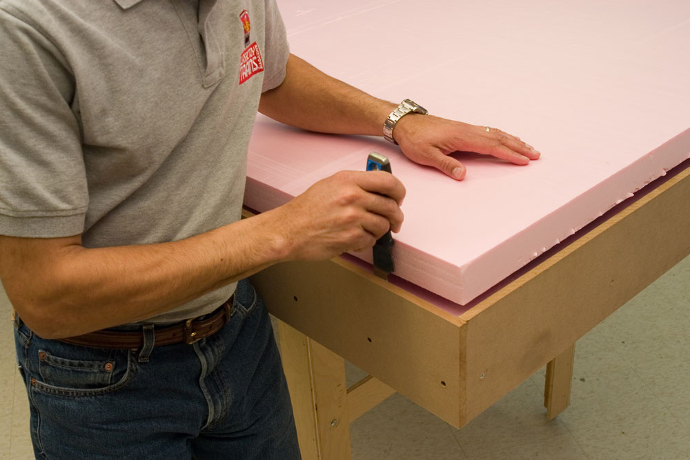 Man building model railroad layout working with pink extruded foam board.