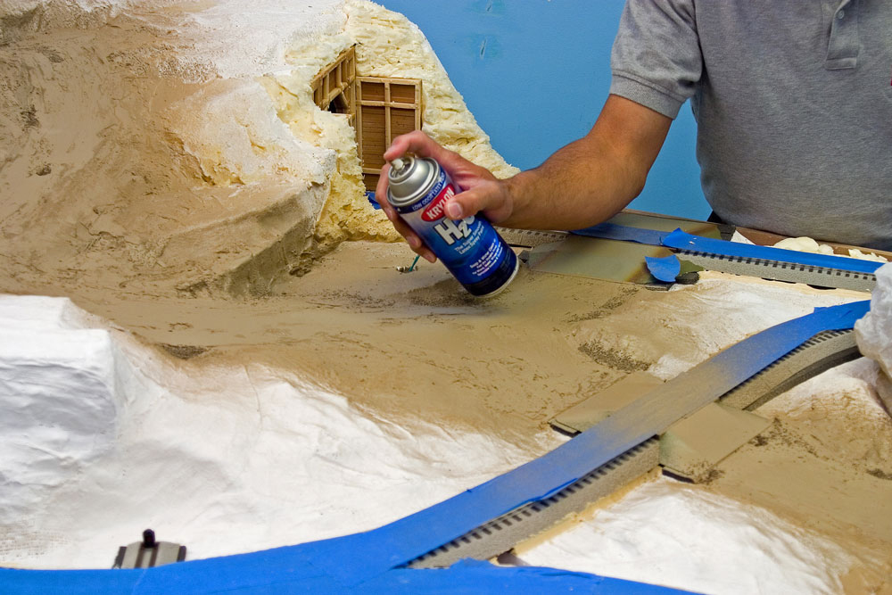 Man painting with water-based spray paint on model railroad layout.