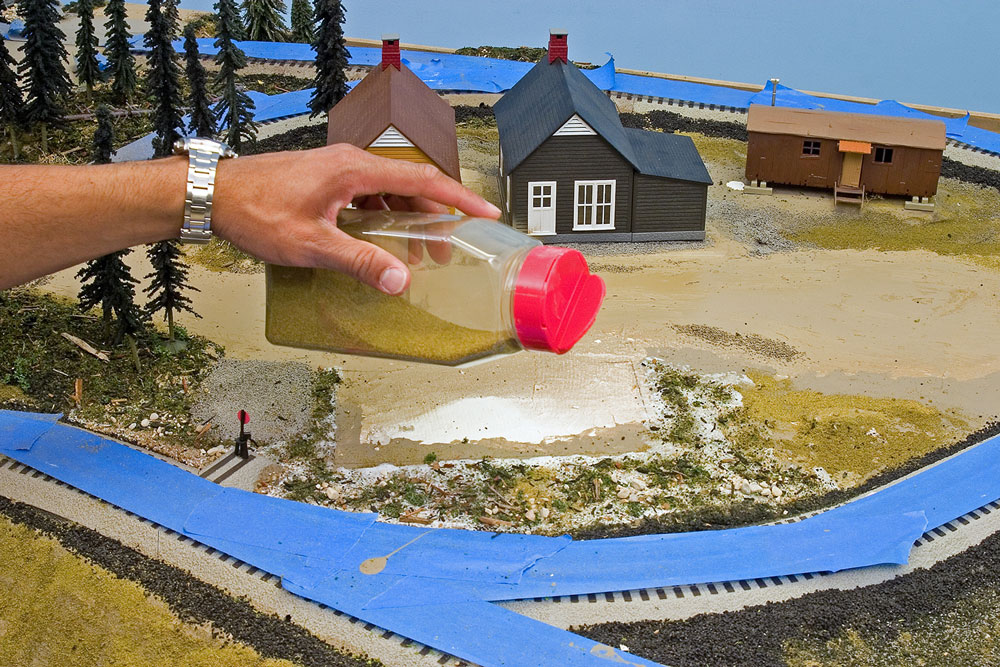 Hand sprinkling green ground foam on model railroad layout.
