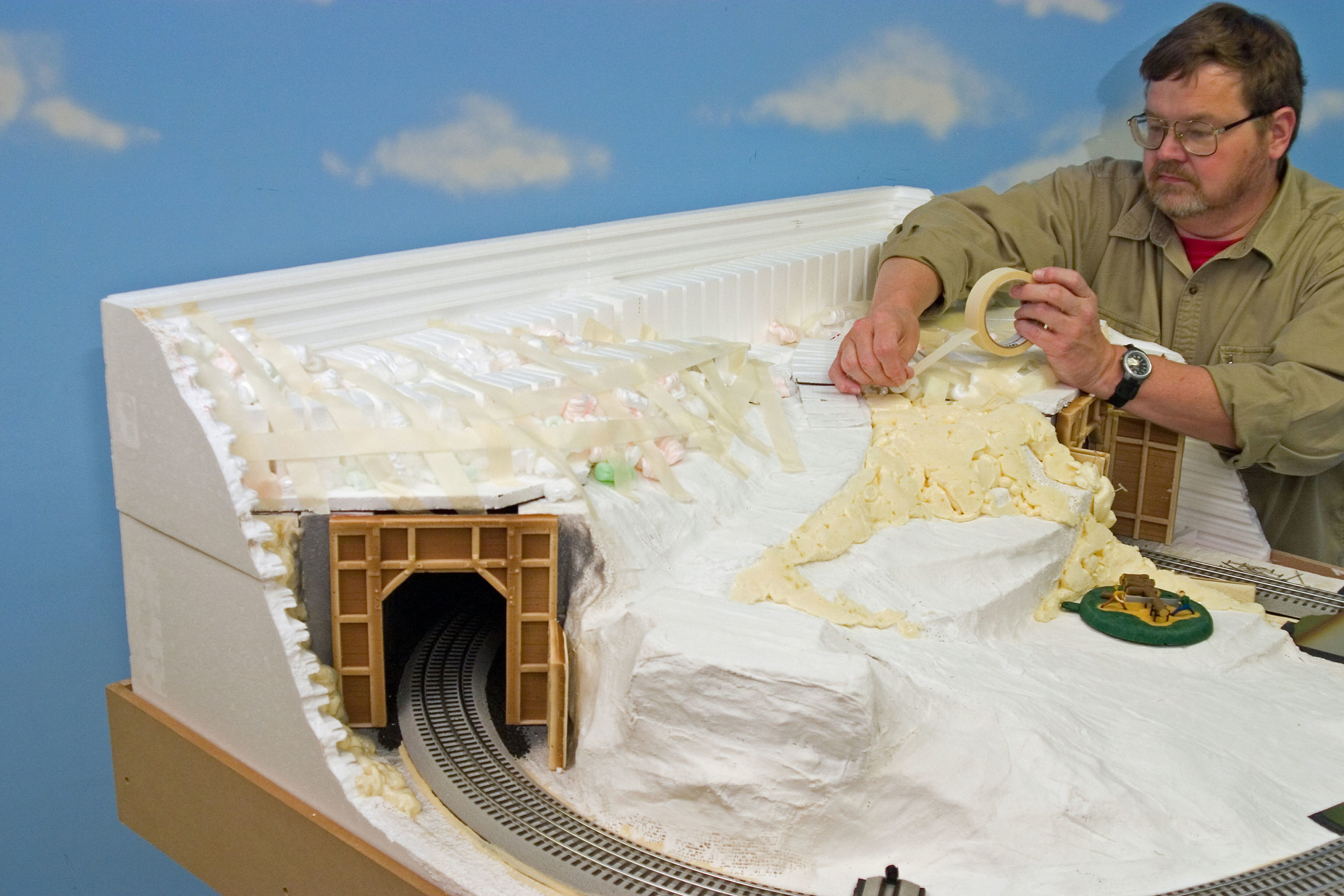 Man working with of foam packing peanuts, expanding foam sealant and profile boards to create a model mountain on a railroad layout.