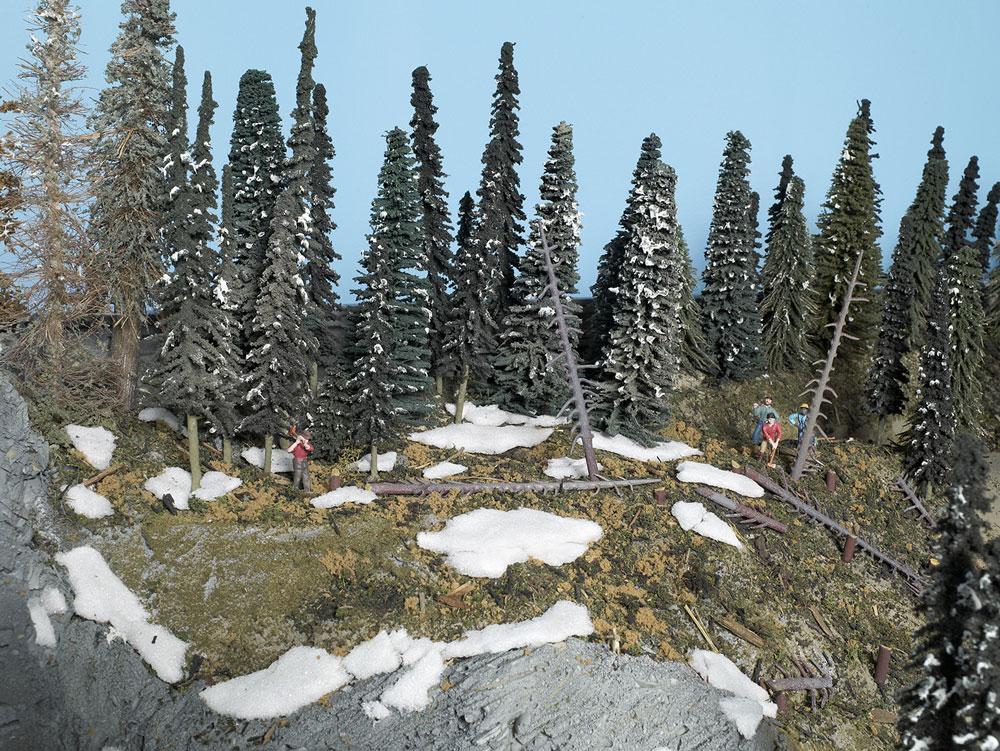 Model scene featuring lumberjack figures, coniferous trees, and Styrofoam resembling melting snow.