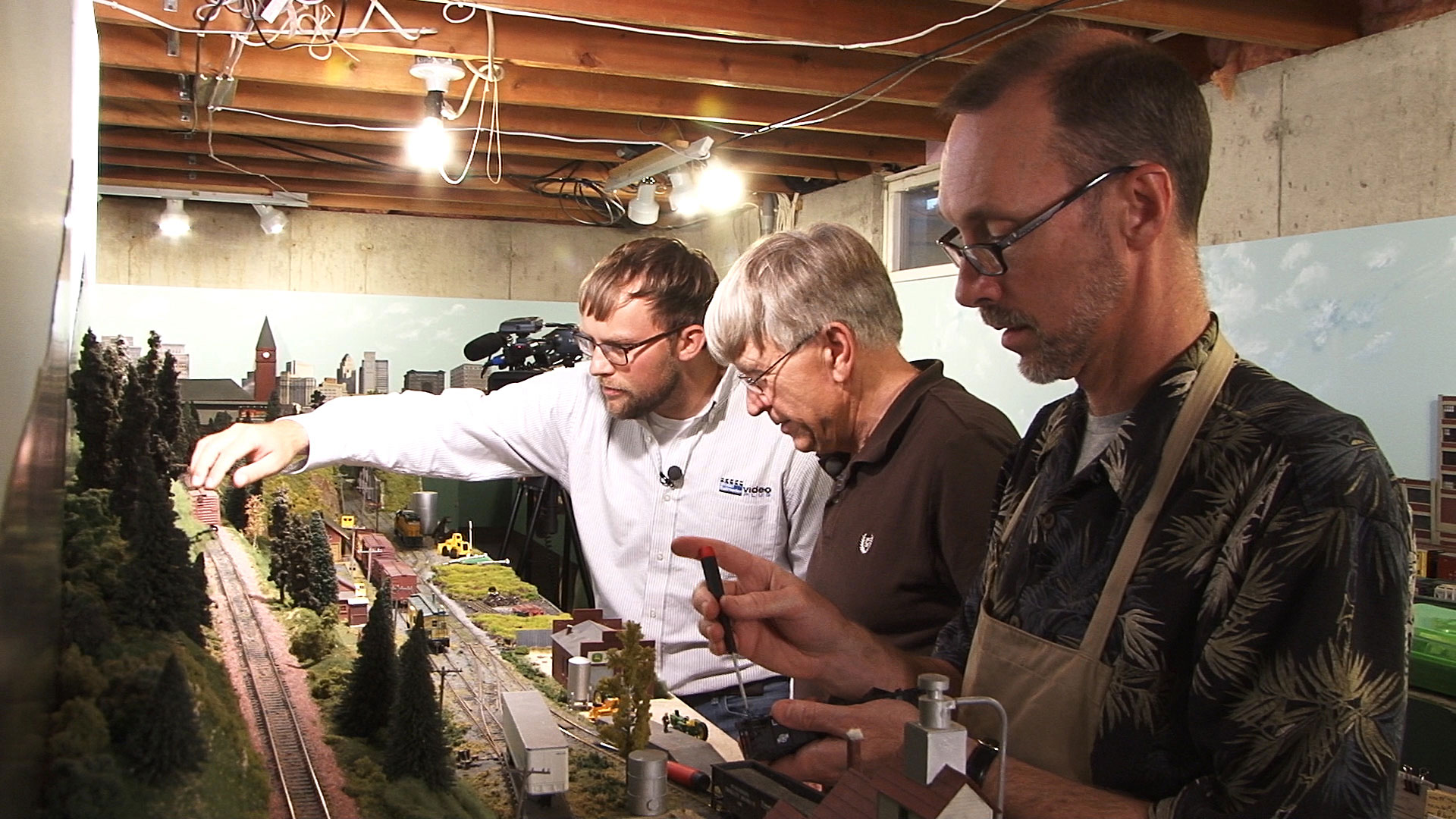 Three people from a model railroader club working together on a layout