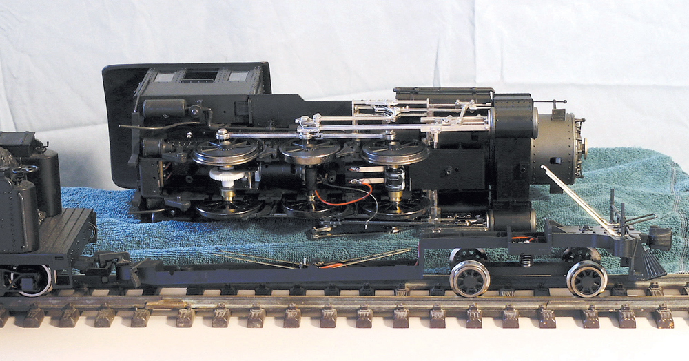 Large-scale model steam locomotive disassembled for lubrication and cleaning.