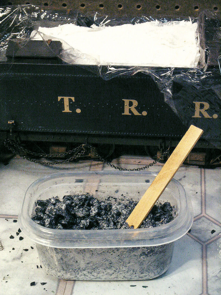 Diluted white glue is mixed with crushed coal to become a load on a model steam locomotive tender.