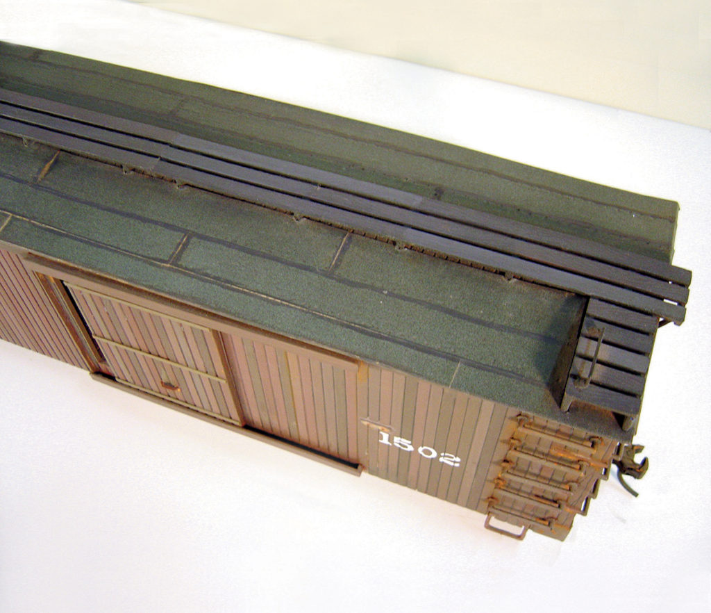 Black masking tape forms a faux tarpaper roof on this boxcar.