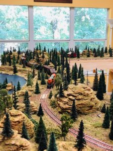 A model train pulling cars through the hilly landscape.