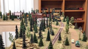 A model train passes by a small town.