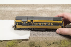Bachmann HO scale Virginian Ry. Fairbanks-Morse H-16-44 diesel locomotive with rear truck on towel wetted with isopropyl alcohol and front truck on rails.