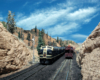 A blue-and-yellow Santa Fe diesel locomotive leads a train through an HO Scale stone walled gorge.