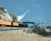 A Union Pacific refrigerated boxcar train gets pushed upgrade in a desert scene west of California's Cajon Pass.