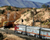 """A Union Pacific train nears the top of the grade in an arid scene at """"Summit"""" in Cajon Pass while a Santa Fe steam locomotive idles near the dispatcher's station."""
