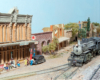 2-6-2 steam locomotives with freight train trundles down dirt-covered tracks in a small-town Western scene.