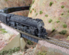 Close-up shot of an HO Scale 4-8-4 Santa Fe steam locomotive hauling an express train through a gorge.