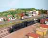 HO Scale Santa Fe steam and diesel locomotives team up to pull a train through a small town scene.