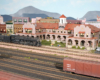 A 4-8-4 Santa Fe steam locomotive poses in front of a Harvey House hotel model amid a multi-tracked yard in a medium-sized city.