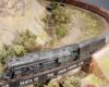 A heavy-duty steam-locomotive, likely a 2-10-4 hauls a train upgrade over a bridge on a Santa Fe-themed layout.