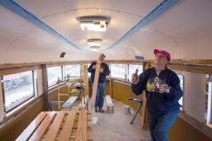 People painting a train car ceiling