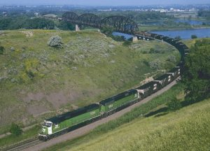 Train coming off bridge on broad curve