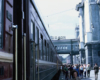 A woman walks toward a camera alongside a train stopped a station.