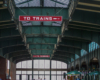"""Green painted steel arches and a glass ceiling focused on  """"To Trains"""" sign."""