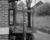 Black-and-white image of wooden baggage cart at an abandoned train station.