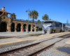An Amtrak train paused at an adobe-style train station under clear skies with palm trees.