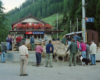 A crowd of people surround a herd of sheep at a makeshift enclosure next to a train station.