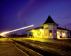 A light blur appears in front of an illuminated passenger train station in the evening.