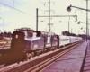 A streamlined electric locomotive hauling a passenger train beside a passenger platform.