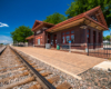 A one-story brick passenger train station appears in sunlight under clear skies in summertime.