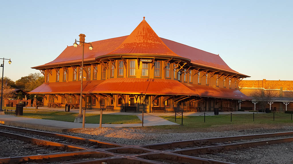 Rounded, old-style passenger train station in low-angle sunlight at a track diamond.