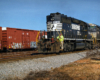 A railroad worker rides the steps of a black diesel locomotive in a yard.