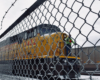 Yellow diesel locomotive behind a chain link fence on a cloudy day.