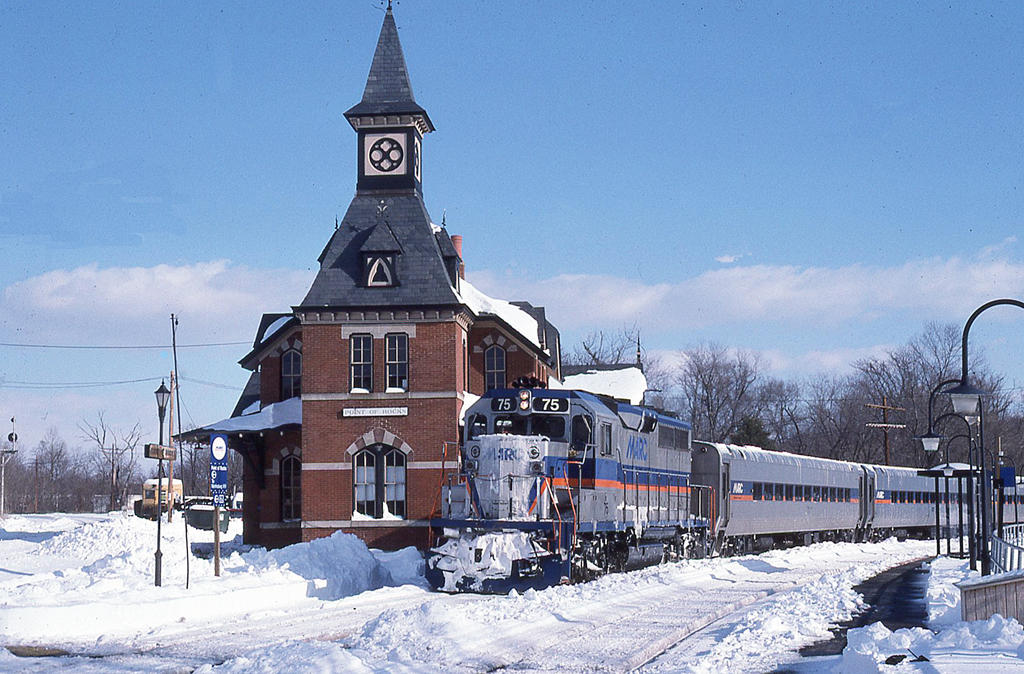 Silver-colored commuter train passes an old-looking passenger train station in the snow.