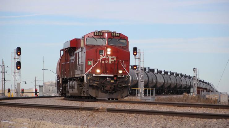 Tank train passing signals on open prairie