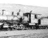 Old 4-6-0 steam locomotive shown in a rail yard.