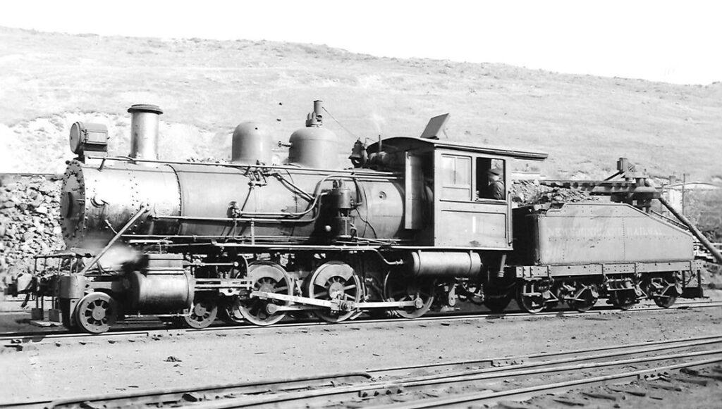 Old 4-6-0 steam locomotive resting in a rail yard.