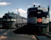 Two cab unit-style diesel locomotives appear in a rail yard.