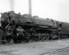 A large steam locomotives pauses in a rail yard.