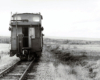 Caboose with open door at the end of a long freight train amid low, rolling field and forest land.