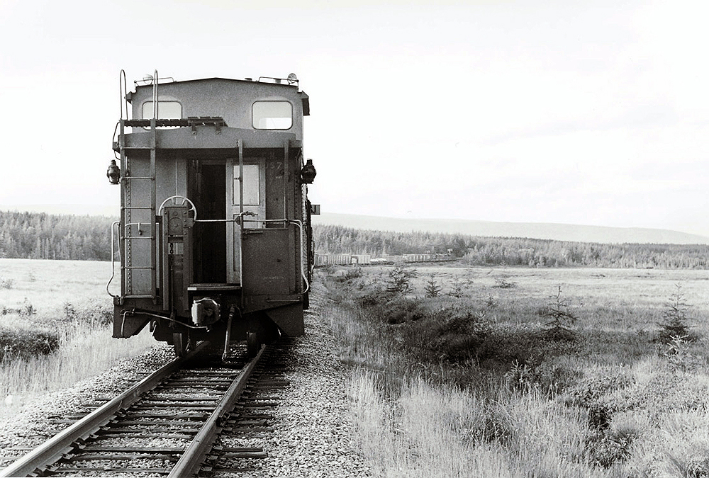 Caboose at rear of freight train in open country