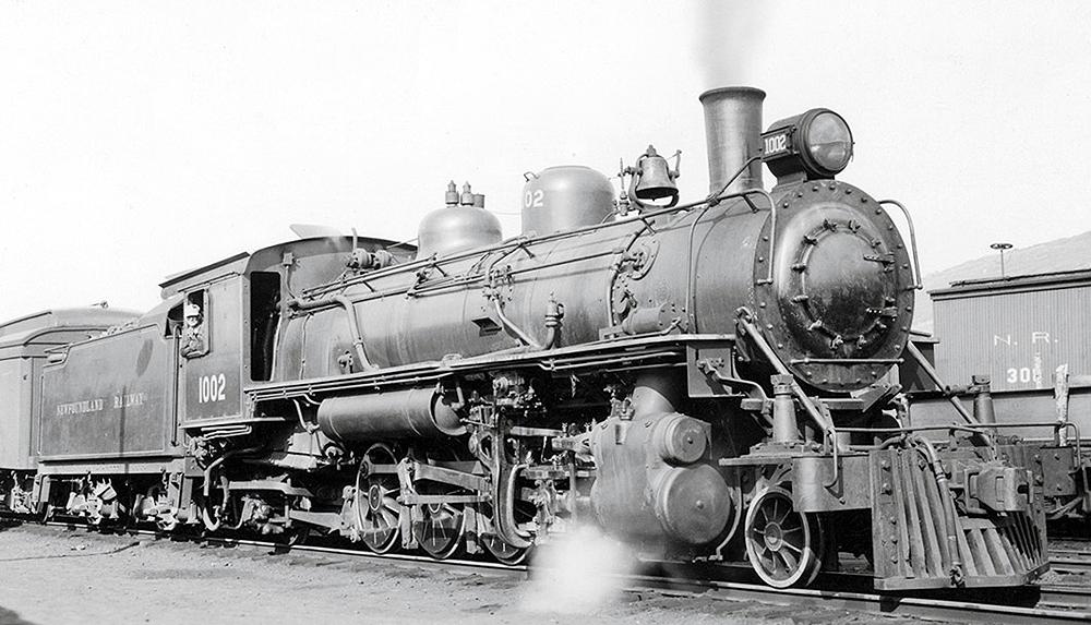 A steam locomotive at the head of a train releasing steam in a rail yard.