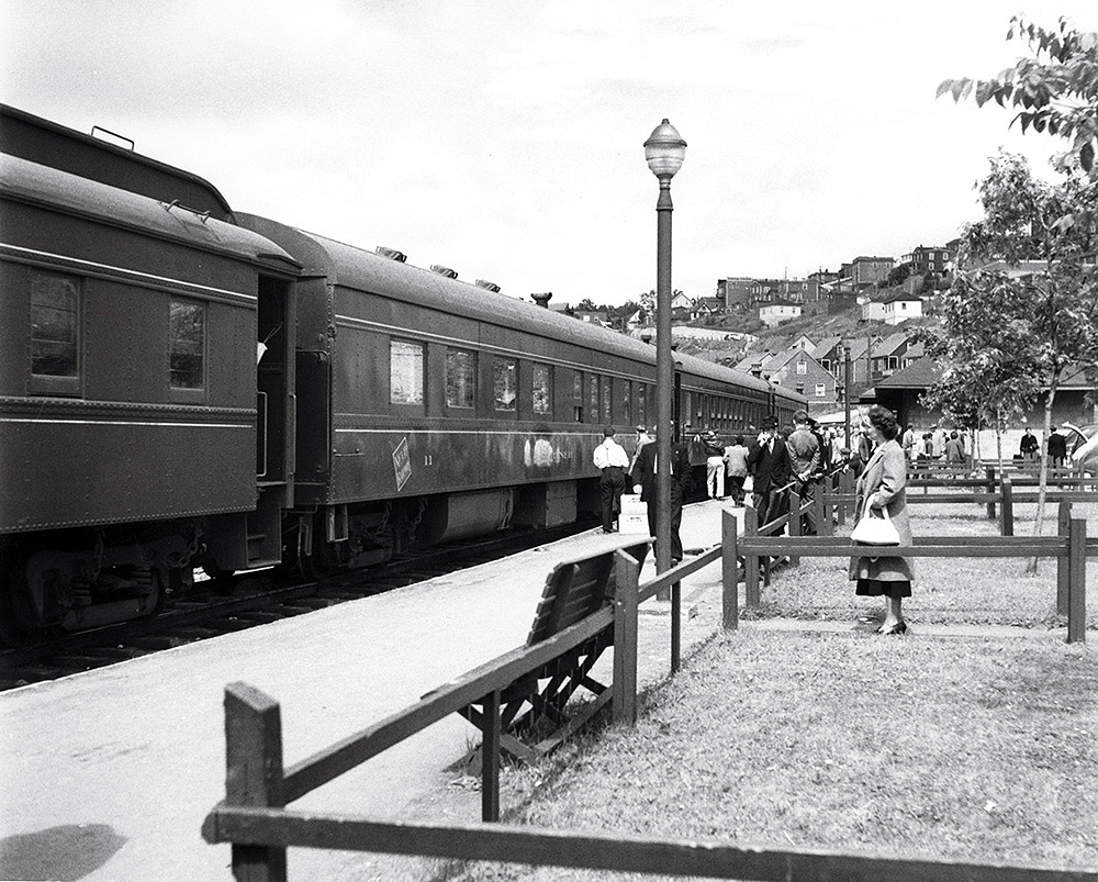 Passenger train at a station surrounded by passengers.