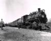 Steam locomotive at the head of a passenger train in a rail yard.