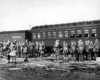 Soldiers in loose formation wearing what appears to be winter clothing in front of a mixed train.