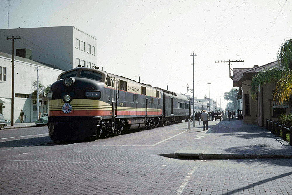Streamlined diesel locomotives with passenger train at station .