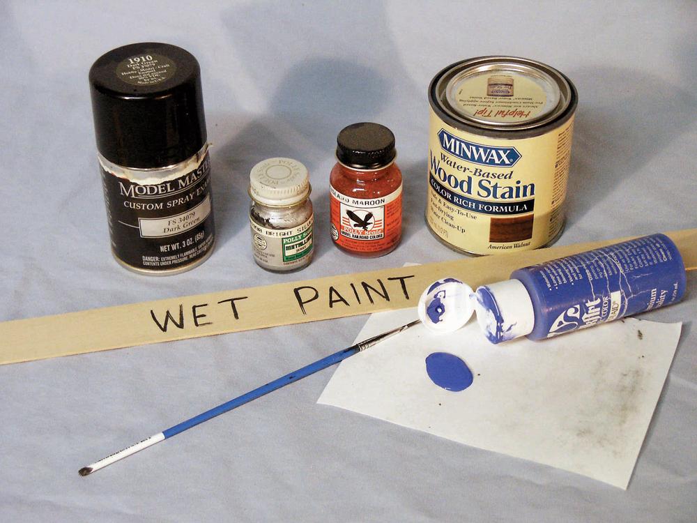 """Assortment of paints plus a paint stir stick labeled """"wet paint."""""""
