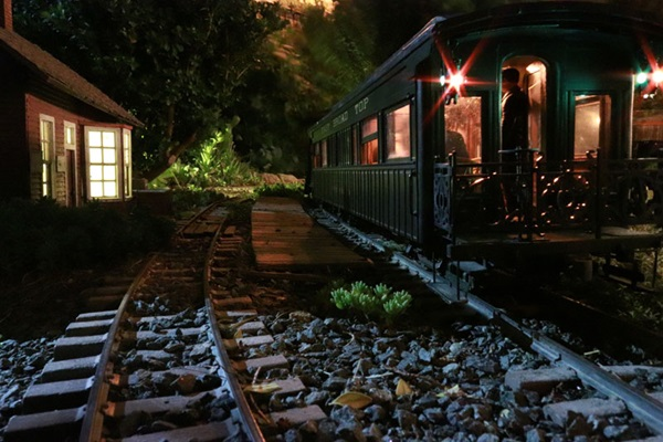 Nighttime trackside scene with lit station