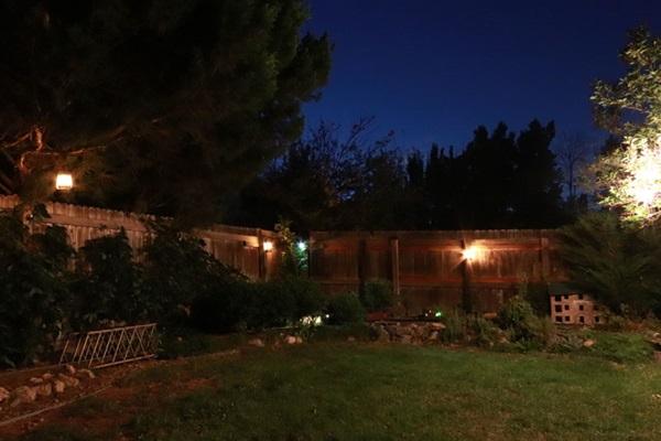A backyard at night, with lanterns providing background light