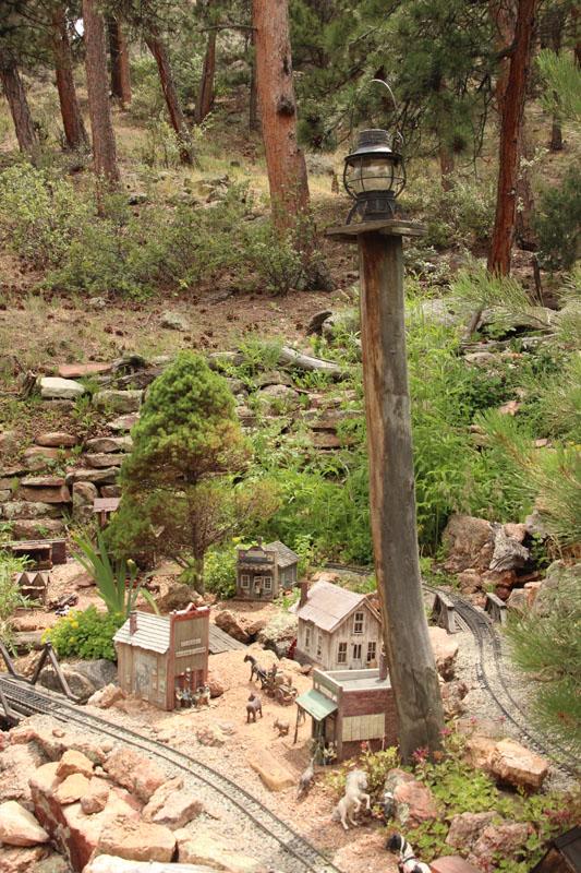 Garden railroad scene with lanterns on posts for nighttime lighting
